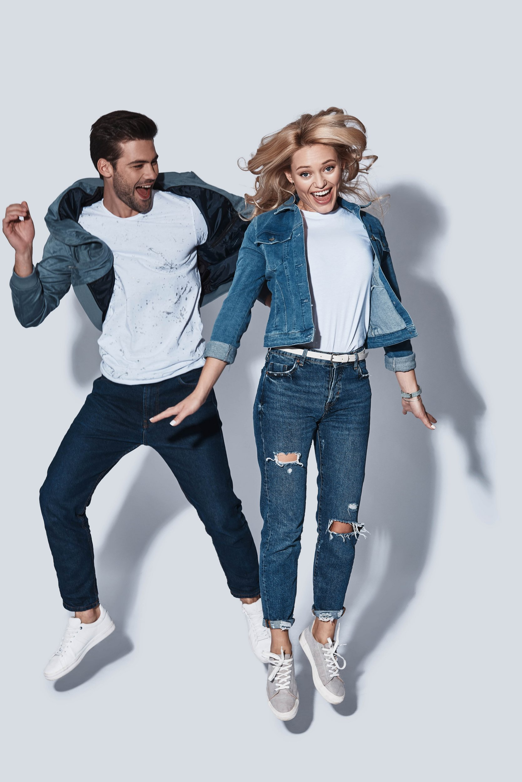 Jumping couple wearing jeans an t-shirts
